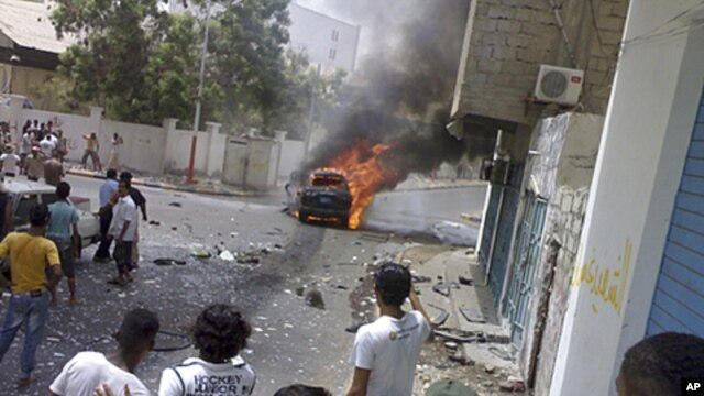 By-standers watch as a booby-trapped car burns after an explosion in the southern Yemeni port city of Aden, July 20, 2011