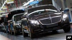 FILE - A Mercedes-Benz AG employee checks a S-Class model at the plant in Sindelfingen, Germany, Jan. 28, 2015. The pact between the world's largest maker of premium cars and the world's largest automotive supplier forms a powerful counterweight to ride-hailing firms Uber and Didi, which are also working on self-driving cars.