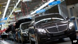 FILE - A Mercedes-Benz AG employee checks a S-Class model at the plant in Sindelfingen, Germany, Jan. 28, 2015.