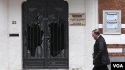 Seorang pria melewati pintu masjid Reda yang rusak di Brussels, Belgia (13/3).