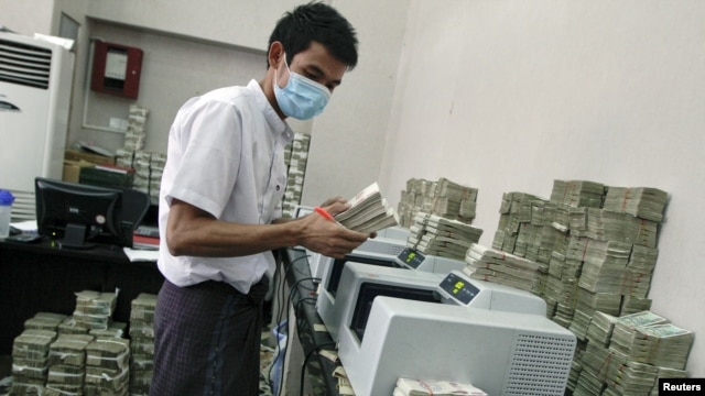 An employee counts Burmese kyat banknotes in a bank in the capital, Rangoon, April 5, 2012.