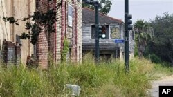 Destroyed buildings and overgrown weeds are seen from Flood St. looking toward Caffin St. in New Orleans, August 25, 2011.