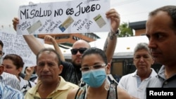 "FILE - People hold a sign that reads ""My health is not a game"" during a protest against shortages of medicines outside a pharmacy in Caracas, Venezuela June 29, 2016."