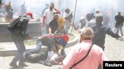 Partidarios del gobierno atacan a una persona frente a la Asamblea Nacional de Venezuela en Caracas, el miércoles, 5 de julio de 2017.