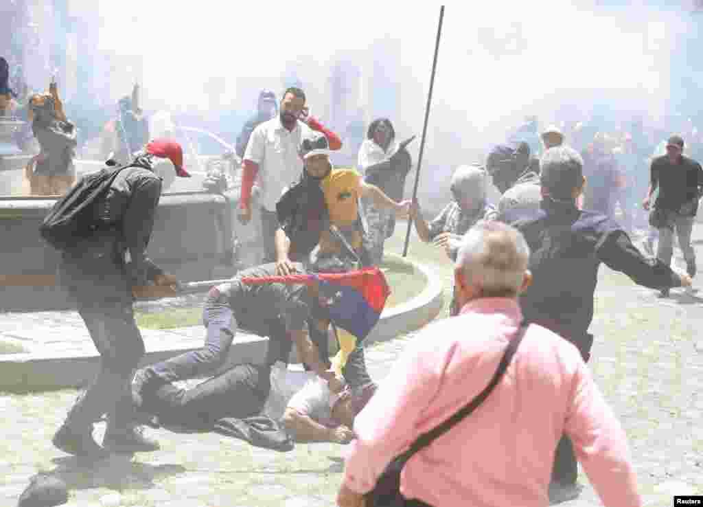 صدر مدورو کے حامی اسمبلی کے باہر ایک شخص کو تشدد کا نشانہ بنا رہے ہیں۔ زخمی ہونے والوں میں حزبِ اختلاف کے پانچ ارکانِ اسمبلی بھی شامل ہیں