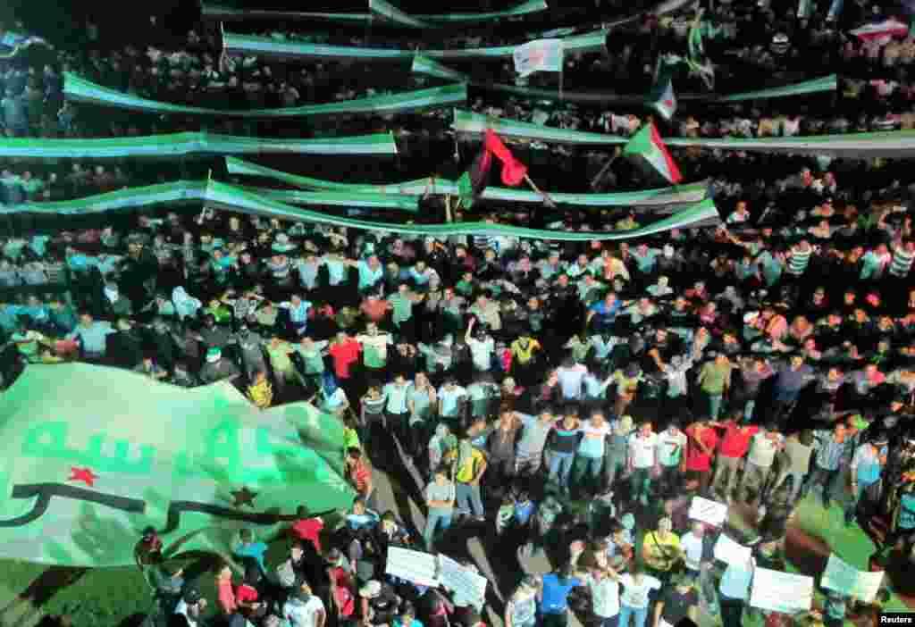 Para demonstran membawa bendera oposisi dalam sebuah protes menentang rezim Presiden Bashar al-Assad di distrik Kfr Suseh di Damaskus (10/7).