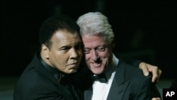 Former boxer Muhammad Ali, left, hugs former U.S. President Bill Clinton as he walks onstage at the grand opening gala celebration for the Muhammad Ali Center, Saturday, Nov. 19, 2005, in Louisville, Ky. (AP Photo/Ed Reinke)