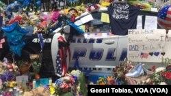 Cientos de personas se acercan al departamento de la policía de Dallas, para ofrecer sus muestras de apoyo. [Foto: Gesell Tobias, VOA].