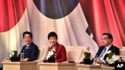 ປະທານາທິບໍດີ ເກົາຫຼີໃຕ້ ທ່ານນາງ Park Geun-hye, ກາງ, ນາຍົກລັດຖະມົນຕີ ຍີ່ປຸ່ນ ທ່ານ Shinzo Abe, ຊ້າຍ, ແລະ ປະທານປະເທດ ຈີນ ທ່ານ Li Keqiang ເຂົ້າຮ່ວມໃນ ກອງປະຊຸມສຸດຍອດທຸລະກິດໃນນະຄອນຫຼວງ ໂຊລ. 1 ພະຈິກ, 2015. ບັນດາຜູ້ນຳທັງສາມ ໄດ້ພົບປະກັນເປັນຄັ້ງທຳອິດໃນກອງປະຊຸມສຸດຍອດໃນເວລາຫຼາຍກວ່າ 3 ປີໃນຂະ ນະທີ່ມະຫາອຳນາດເອເຊຍຕາເວັນ ອອກສຽງເໜືອ ດີ້ນຮົນເພື່ອຊອກຫາຄວາມ ຄິດເຫັນຖ້າມກາງການຂັດແຍ້ງກັນກ່ຽວກັບ ປະຫວັດສາດ ແລະ ການຂັດແຍ້ງເຂດແດນ.