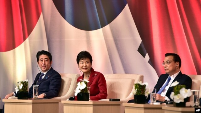 South Korean President Park Geun-hye, center, Japanese Prime Minister Shinzo Abe, left, and Chinese Premier Li Keqiang attend at a business summit in Seoul, Nov. 1, 2015. The leaders met for their first summit talks in more than three years as the Northeast Asian powers struggle to find common ground amid bickering over history and territory disputes.