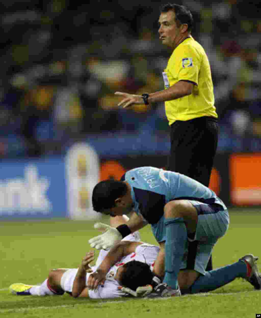 Tunisia's goalkeeper Mathlouthi Ayem attends to injured teammate Jemal Ammar as referee Daniel Bennett from South Africa calls for assistance during their African Cup of Nations Group C soccer match against Morocco at Stade De L'Amitie Stadium in Librevil