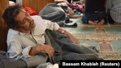 FILE - A survivor from what activists say is a gas attack rests inside a mosque in the Duma neighborhood of Damascus, August 21, 2013.