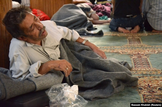 FILE – A survivor of what activists say was a gas attack rests in a mosque in Damascus' Duma neighborhood, Aug. 21, 2013.