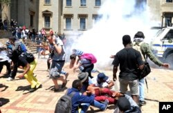 Students and police clash on the University of the Witwatersrand campus in Johannesburg South Africa on Monday, Oct. 10, 2016.