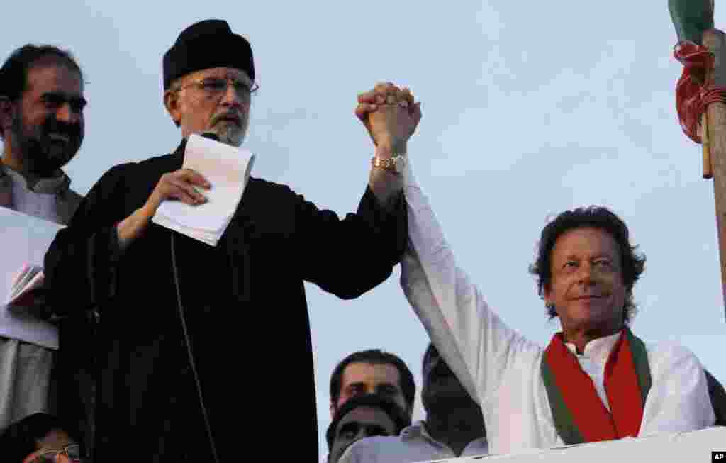 Pakistan's fiery cleric Tahir-ul-Qadri (second left) and cricketer-turned-politician Imran Khan (right), jointly raise their hands for their supporters during a protest near the prime minister's home in Islamabad, Sept. 2, 2014.