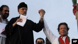 FILE - Pakistan's fiery cleric Tahir-ul-Qadri, second left, and cricketer-turned-politician Imran Khan, right, jointly raise their hands for their supporters during a protest near Prime Minister's home in Islamabad.