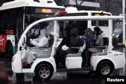湖北武漢一所醫院外身穿防護服的工作人員駕駛一輛運送新冠病毒感染者的車輛。(2020年2月15日)