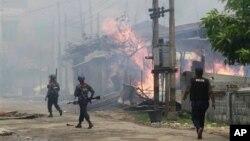 Pasukan keamanan Burma melewati sebuah perkampungan warga muslim yang dibakar di Sittwe, ibu kota negara bagian Rakhine (foto: dok).