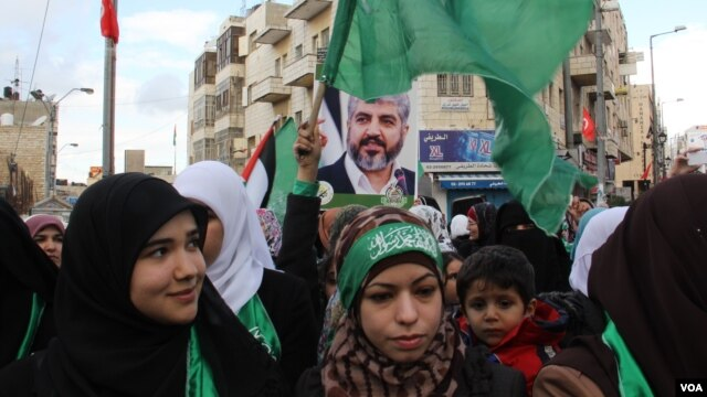 Hamas supporters, some carrying posters of the group's leader, Khaled Meshaal, rally in the West Bank, December 14, 2012. (VOA/R. Collard)