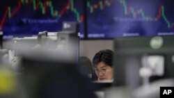 A trader watches the computer monitors in Seoul, South Korea. Online trading can easily be done at home and has increased during under coronavirus measures. File (AP Photo/Lee Jin-man)