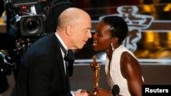 """Lupita Nyong'o entrega o Oscar de Melhor Actor Secundário a J.K. Simmons pelo filme """"Whiplash"""" nos Oscar 2015"""