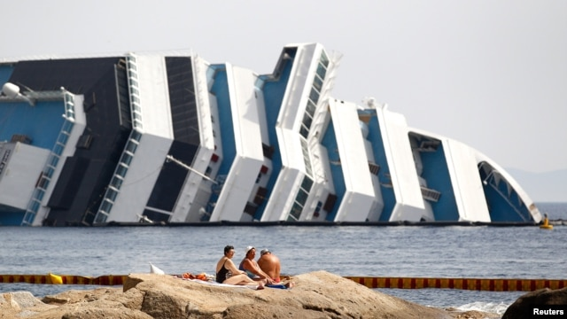 June 20, 2012: Vacationers bask in front of the wreckage of capsized cruise liner Costa Concordia near the harbour of Giglio Porto.