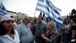Protesters holding national flags take part in an anti-austerity rally in front of the parliament in Athens, Greece, June 17, 2015.