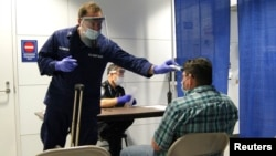 U.S. Coast Guard Health Technician Nathan Wallenmeyer (L) and Customs Border Protection (CBP) Supervisor Sam Ko conduct pre-screening measures on a passenger arriving from Sierra Leone at O'Hare International Airport's Terminal 5 in Chicago, Illinois, Oct. 16, 2014.