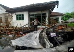 Seorang petugas polisi memeriksa kerusakan rumah anggota Ahmadiyah setelah diserang di Pandeglang, Banten, Senin, 7 Februari 2011. (Foto: AP)