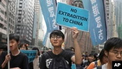 FILE - Protesters with placards and flags against an extradition law march toward the government headquarters in Hong Kong, March 31, 2019.