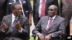 Ông Emmerson Mnangagwa, trái, trò chuyện với Tổng thống Zimbabwe Robert Mugabe sau lễ tuyên thệ tại Harare, 12/12/2014.