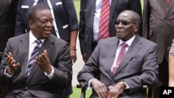 FILE - Emmerson Mnangagwa, left, Vice President of Zimbabwe chats with Zimbabwean President Robert Mugabe after the swearing in ceremony at State House in Harare, Dec, 12, 2014.