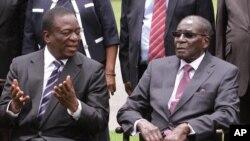 Emmerson Mnangagwa, à gauche, le vice-président du Zimbabwe discute avec le président zimbabwéen Robert Mugabe après la cérémonie de prestation de serment à State House à Harare, le 12 décembre 2014.