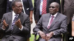 FILE: Emmerson Mnangagwa, left, Vice President of Zimbabwe chats with Zimbabwean President Robert Mugabe after the swearing in ceremony at State House in Harare, Dec, 12, 2014.