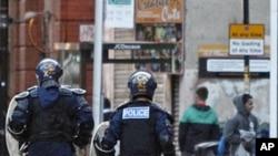 图为英国防暴警察8月9日在曼彻斯特追赶打劫商店的人