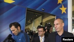 Greek Finance Minister Yanis Varoufakis (R) leaves the European Commission headquarters in Brussels, May 5, 2015.