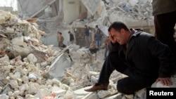 Một người đàn ông ngồi khóc tại một địa điểm bị trúng phi đạn Scud tại Ard al-Hamra thuộc thành phố Aleppo, 23/2/2013