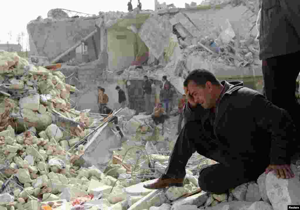 A man cries at a site hit by what activists said was a Scud missile in Aleppo's Ard al-Hamra neighborhood, Syria.
