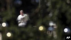 El Papa Francisco, enmarcado por el arbol de Navidad en la Plaza de San Pedro, elogió las escenas de la Natividad como un símbolo de la fe cristiana, AP