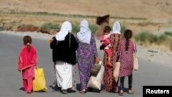 Phụ nữ và trẻ em người Yazidi chạy trốn bạo lực ở Iraq đi bộ trong trại tị nạn ở tỉnh Dohuk, biên giới Syria-Iraq, ngày 14/8/2015.