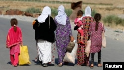 FILE - Women and children from the minority Yazidi sect, fleeing the violence in the Iraqi town of Sinjar, walk to a refugee camp after they re-entered Iraq from Syria at the Iraqi-Syrian border crossing in Fishkhabour, Dohuk province, Aug. 14, 2014.