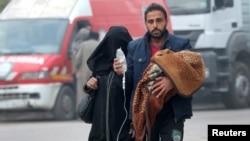 مشرقی حلب سے ایک شہری اپنے خاندان کے ساتھ محفوظ مقام کی طرف جا رہا ہے۔ 12 دسمبر 2016