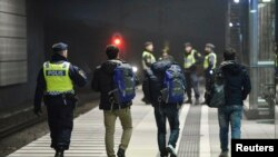 Un officier de police escorte des migrants du train de la gare de Hyllie à Malmo, en Suède, le 19 novembre 2015.