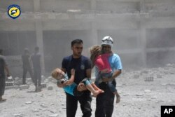 This photo provided by the Syrian Civil Defense group known as the White Helmets, shows civil defense workers carrying children after airstrikes hit a school housing a number of displaced people, in the western part of the southern Daraa, Syria, June 14, 2017.
