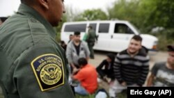 In this Thursday, March 14, 2019, file photo, a Border Patrol agent talks with a group suspected of having entered the U.S. illegally near McAllen, Texas. (AP Photo/Eric Gay, File)