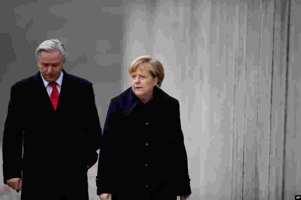 German Chancellor Angela Merkel, right, and Mayor of Germany's capital Berlin, Klaus Wowereit walk along remains of the Berlin Wall at the Berlin Wall memorial site at Bernauer Strasse in Berlin, Germany.