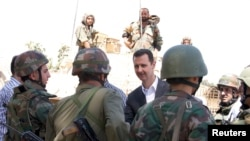 Syria's President Bashar al-Assad, center, chats with military personnel during visit to military site in Daraya,Aug. 1, 2013, SANA handout photo.