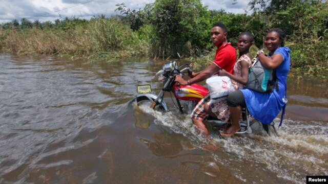 A man rides a motorcycle with passengers along a flooded road in the Patani community in Nigeria's Delta state, October 15, 2012.