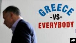 """Pešak prolazi pored grafita """"Grčka protiv svih"""" ispisanog na zid banke u Atini"""