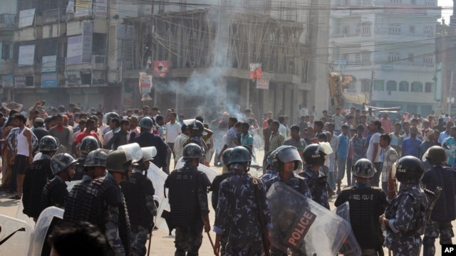 FILE - Ethnic Madhesi protesters stand near smoke from a tire set on fire by them, as Nepalese policemen stand guard near the Central Development Office at Birgunj, a town on the border with India, Nepal, Nov. 2, 2015.